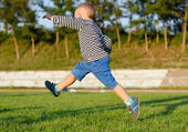 Little boy midair kicking a ball — Stock Photo