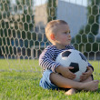 Little boy with a soccer ball on his lap — Stock Photo #13628289