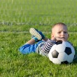 Boy lying on grass with soccer ball — Stock Photo #13628291