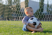 Little boy with a soccer ball on his lap — Stock Photo