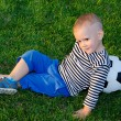 Stock Photo: Youngster lying against his soccer ball