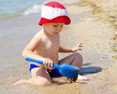 Liten pojke spelar i grunda surf — Stockfoto
