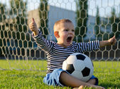 Boy with football shouting with glee — Stockfoto