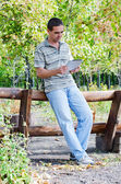 Man leaning on a timber fence with a tablet — Stock Photo