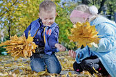 Children collecting yellow fall leaves — Stock Photo