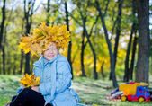 Smiling young girl with hat of autumn leaves — Stock Photo