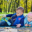 Young Children Laying on the Ground in a Park — Stock Photo