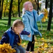 Laughing children playing with fall leaves — Stock Photo