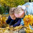 Kids searching amongst autumn leaves — Stock Photo