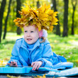 Beautiful little girl with crown of autumn leaves — Stock Photo