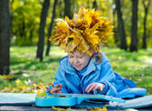 Little girl with a hat of yellow autumn leaves — Stock Photo