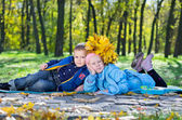 Little kids lying close together in an autumn park — Stock Photo