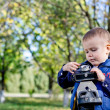 Stock Photo: Little boy playing with a vintage camera