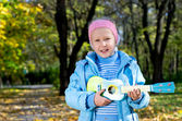 Happy little girl strumming a toy guitar — Stock Photo