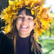 Laughing woman wearing autumn leaves — Stock Photo