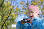 Small girl intrigued by an old camera — Stock Photo