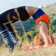 Active Young Blonde Woman Doing Yoga Outdoors - Stock Photo