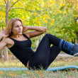 Beautiful Blonde Woman Exercising on Yoga Mat - Stock Photo