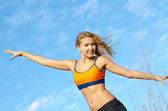 Athletic woman with her arms outstretched — Stock Photo