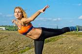 Athletic woman balancing on one leg — Stock Photo