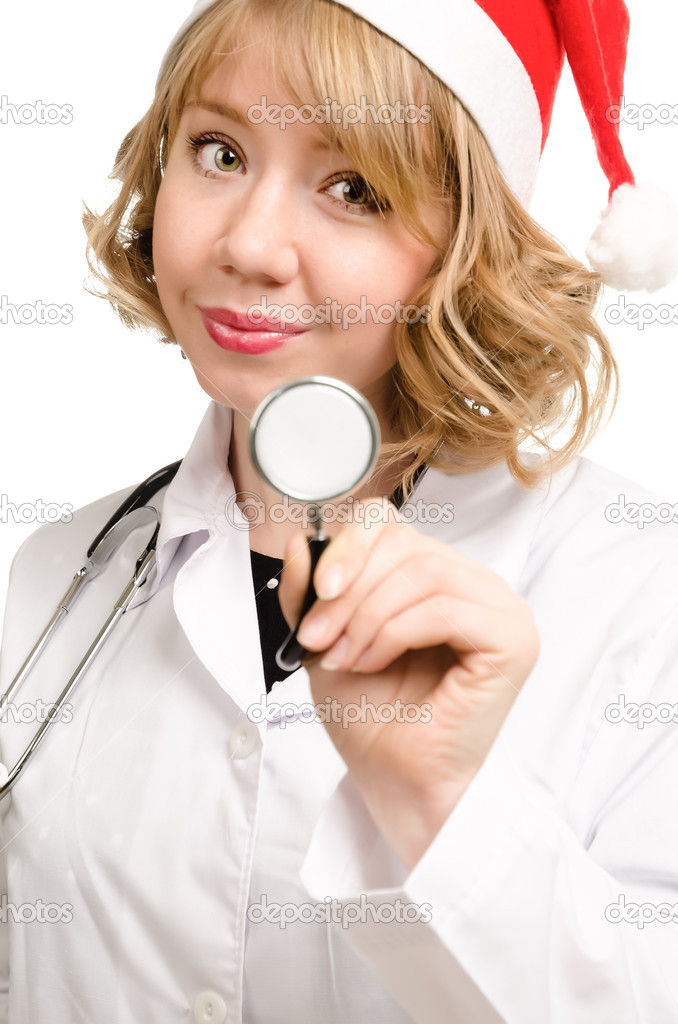 Pretty young blonde female doctor in a Santa Claus hat holding up the disc of a stethoscope as she prepares to start her examination — Stock Photo #16096845