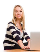 Attractive blonde woman at her laptop — Stok fotoğraf