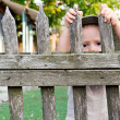 Boy looking through a fence — Stock Photo