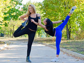 Two young women exercising in a park — Stock Photo