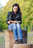 Kobieta siedzi na pniu drzewa, czytanie — Zdjęcie stockowe