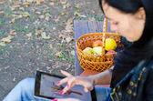 äpplen tillsammans med en kvinna med en tablett — Stockfoto