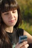 Kobieta czytająca wiadomości tekstowej na jej telefon komórkowy — Zdjęcie stockowe