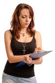 Young woman writing on a clipboard — Stock Photo