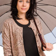 Beautiful woman sheltering under an umbrella — Stock Photo