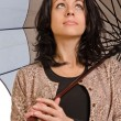 Beautiul brunette sheltering under her umbrella - Stock Photo