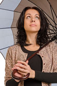 Beautiul brunette sheltering under her umbrella — Stock Photo