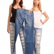 Two young women holding up a pair of jeans — Stock Photo