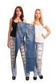 Dvě mladé ženy drží džíny — Stock fotografie