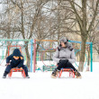 Mother and son sledding in winter — Stock Photo