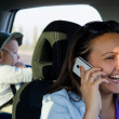 Woman driver laughing on her mobile phone — Stock Photo #19777125