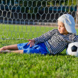 Small boy lying in the goalposts — Stock Photo