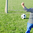 Young boy kicking soccer ball — Stok Fotoğraf #19777171