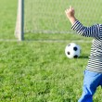 Young boy kicking a soccer ball — Stock Photo