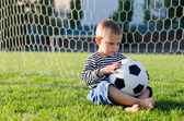 Thoughtful little boy with a soccer ball — Stock Photo