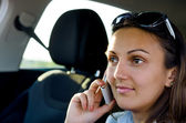 Woman using her mobile in a car — Stock Photo