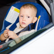 Little boy in a child safety seat sitting patiently in the back of a car — Stock Photo