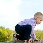 Little boy exploring climbing a rock — Stock Photo #20184725