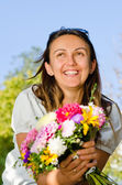 Happy laughing woman with flowers — Stock Photo