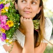 Beautiful woman with flowers daydreaming — Lizenzfreies Foto