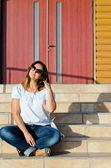 Happy woman sitting on steps — Stock Photo