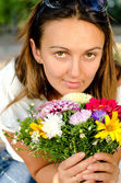 Beautiful woman with colourful flowers — Stock Photo